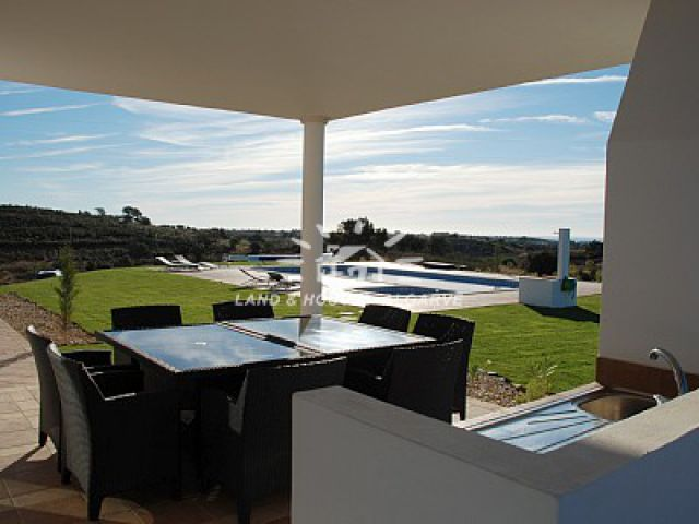 Alfresco diner on covered terrace next to BBQ